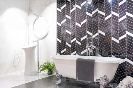 Modern bathroom interior with minimalistic shower and lighting, white toilet, sink and bathtub