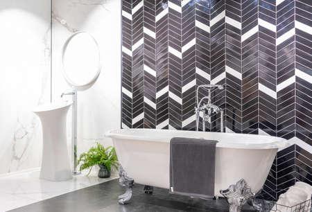 Modern bathroom interior with minimalistic shower and lighting, white toilet, sink and bathtub Фото со стока - 151694070