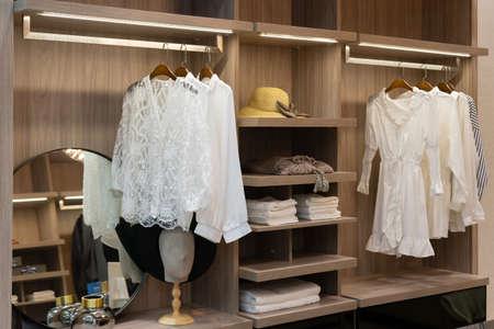 modern wooden wardrobe with women clothes hanging on rail in walk in closet, Scandinavian style Фото со стока - 151694580