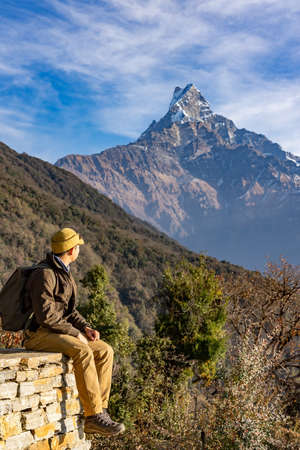 A man trekker is enjoying the view of Machapuchare and Mardi himal peak in the Annapurna Himalayas of north central Nepal. Фото со стока - 151694814