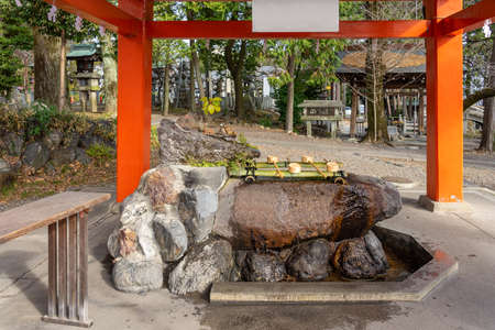 Washing Bamboo fountain Pool with a wooden bucket in Japanese Temple. Water basin for hands and mouth cleansing ritual before entering holy shrine Фото со стока - 151694714