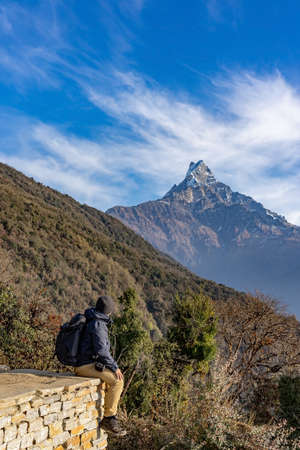 A man trekker is enjoying the view of Machapuchare and Mardi himal peak in the Annapurna Himalayas of north central Nepal. Фото со стока