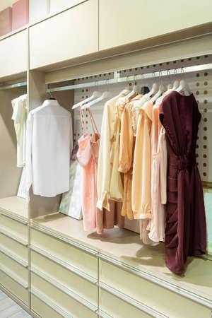 Modern wooden wardrobe with women clothes hanging on rail in walk in closet, Scandinavian style Фото со стока - 151694729