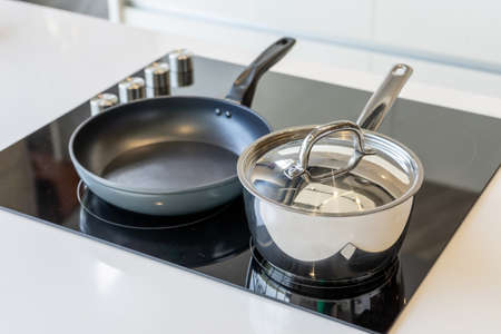 Close-up of stainless steel cooking pot and pan on induction hob in modern kitchen. modern kitchen pot cooking induction electrical stove hob concept Фото со стока - 151694874