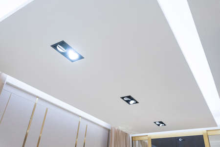 look up on suspended ceiling with halogen spots lamps and drywall construction in empty room in apartment or house. Stretch ceiling white and complex shape. Фото со стока - 151695125