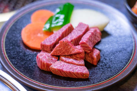 Hida beef (Hida gyu) is one of the best beef in Japan. Raw beef slice on grille for barbecue or Japanese style yakiniku Фото со стока