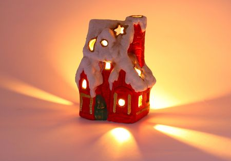 tiny red xmas house with chimney, snow and candlelight