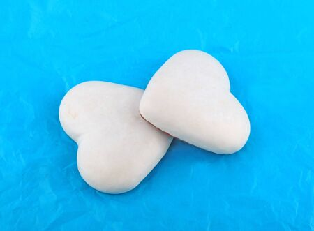 couple of white honey-cakes hearts over blue paper Stock Photo