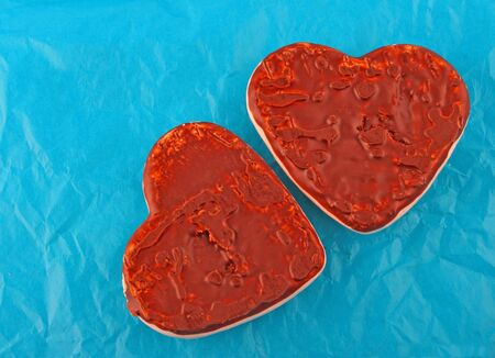 spicecake: two chocolate honey-cakes hearts over blue paper