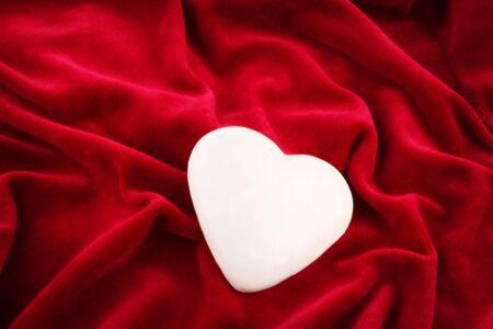 lonely shining white heart over purple velvet