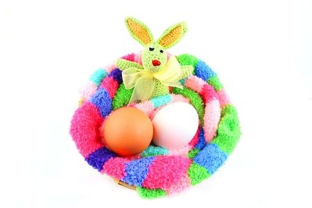easter bunny and two eggs in a fluffy multicolored clutch Stock Photo