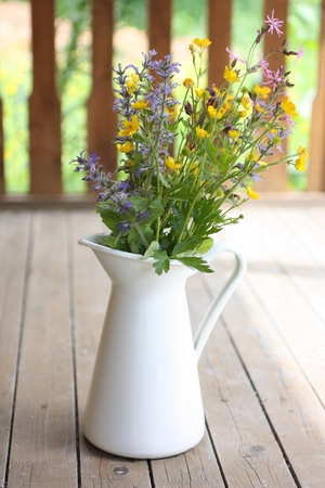 colorful still life: Summer bouquet in a white pitcher on wooden terrace