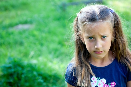 Close-up portrait of a beautiful blonde offended crying little girl on the background of meadows photo