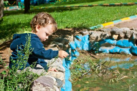 children pond: Cute little boy playing near the pond in the autumn park