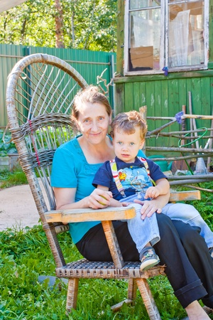 Portrait of grandmother and grandson sitting in cane chair in the garden photo