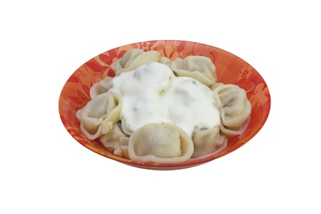 Meat pelmeni with sour cream on the red plate isolated photo