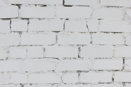 A roughly textured brick wall painted with white paint photo