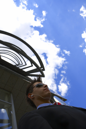 musik: a young business man is listening to his musik while talking a break outside his office