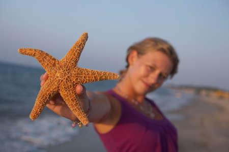 seastar: cute girl is holding up an seastar Stock Photo