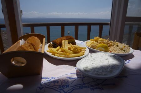 typical greek food on a terrace with an great view to the ocean Stock Photo