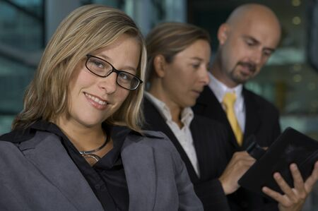 Business woman smiling on front a team