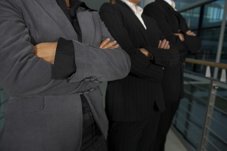 Business Team standing with crossed hands Stock Photo