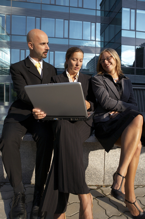 Business Team having a discussion with laptop