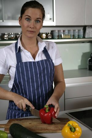 Young woman standing in the kitchen chopping pepper Stock Photo