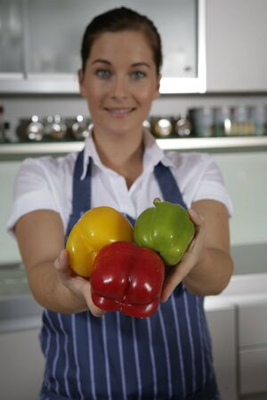Young woman standing in the kitchen presenting peppers