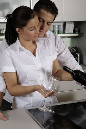 Young attractive couple pouring out wine