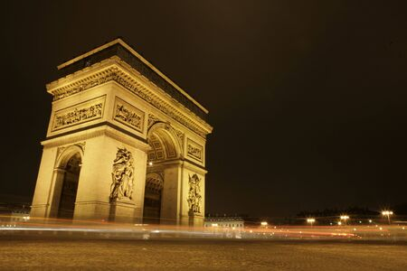 Arc de Triomphe at night with cars driving by Stock Photo