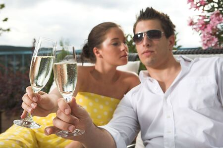 stylish couple celebrating by having a drink on terrace Stock Photo
