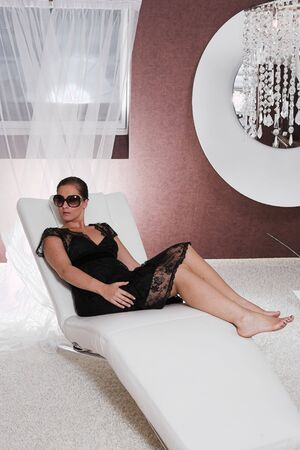 Young attractive Woman with sunglasses posing on couch