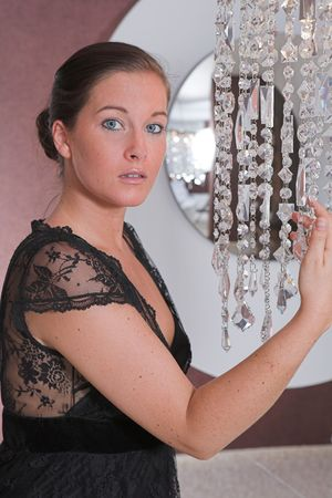 Young attractive Woman posing in front of a mirror with glitter chain Stock Photo