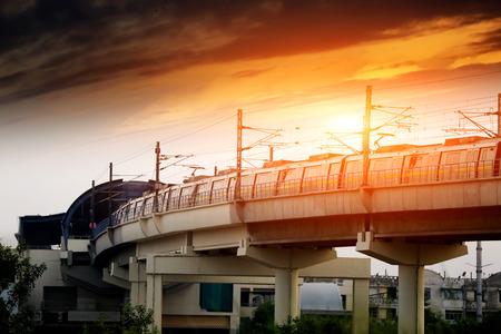 Metro train entering in to the station during sunset under the beautiful cloudscape. Фото со стока