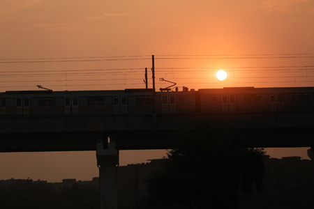 Metro train entering in to the station during sunset silhouette.