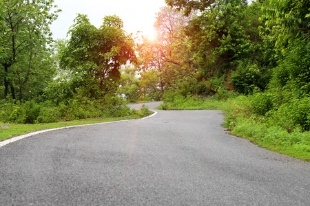 A Beautiful Highway taking curve through the Forest in Mountain Range Located in India.