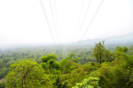 Power supply distribution in the middle of forest located in Uttrakhand, India elevated view. Фото со стока