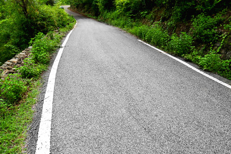 Single lane road taking curve through the Forest in Mountain Range Located in Uttrakhand, India.