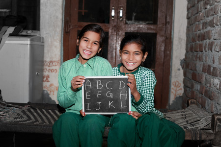 Two Cheerful Little girl sitting on the Charpai at their home holding chalkboard (slate) with English alphabet writing on it, wearing school dress and laughing together portrait.