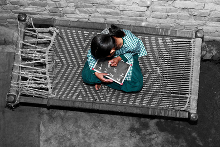 Elevated view of elementary age cheerful School girl of Indian Ethnicity sitting  on cot holding chalkboard wearing school uniform. She is writing alphabet on the chalkboard while sitting on the cot.