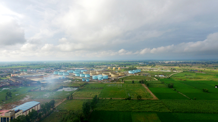 Oil refinery factory in the middle of green fields under the beautiful cloudscape.