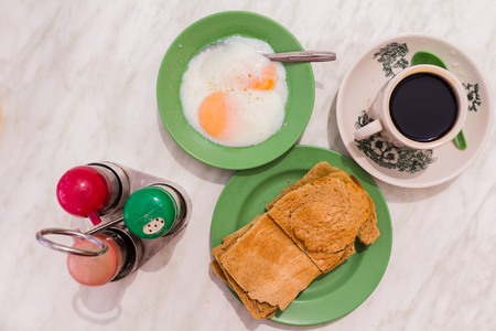 Traditional Singapore Breakfast called Kaya Toast, Coffee bread with Coconut jam and Half-boiled eggs, Oriental Chinese coffee in vintage mug and Original bread toast with kaya a local jam made from eggs, sugar and coconut milk. The fractal on the cup is  Stock Photo