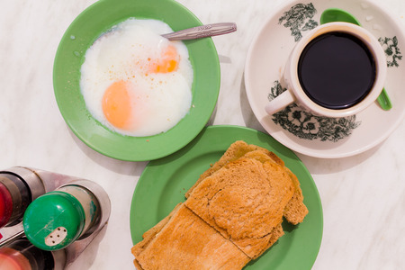 kaya: Traditional Singapore Breakfast called Kaya Toast, Coffee bread with Coconut jam and Half-boiled eggs, Oriental Chinese coffee in vintage mug and Original bread toast with kaya a local jam made from eggs, sugar and coconut milk. The fractal on the cup is  Stock Photo