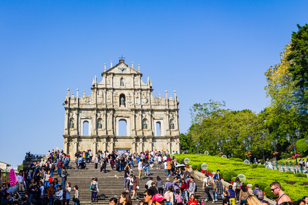 Macao, China - December 9, 2016: Tourists and local residents walk pass and take photos at The Ruins of St. Pauls in sunny day, crowded tourist in blue sky sunny day