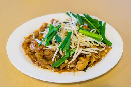 Thai Fried Noodles Pad Thai and vegetables close-up on the table Stock Photo
