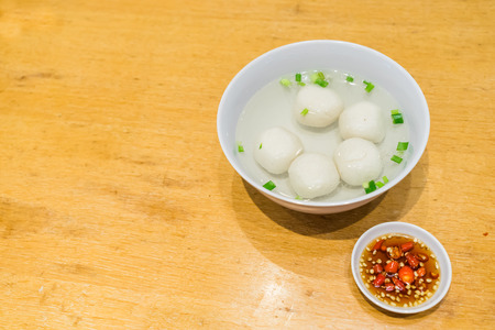 exclusively: Hearty meal of Teowchew Fishball with soup and chili sauce on table, Fishball noodles Made exclusively of fish paste and moulded into balls or fishcake slices