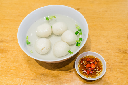 Hearty meal of Teowchew Fishball with soup and chili sauce on table, Fishball noodles Made exclusively of fish paste and moulded into balls or fishcake slices