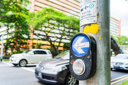 paso de peatones: Botón para el semáforo y los coches en segundo plano. Semáforos en la encrucijada. El botón del mecanismo enciende los semáforos en la calle. Cierre de intersección del semáforo de control del sistema.