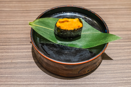 Uni Sushi, Sea Urchin Japanese food in black plate and leaf on wooden table Stock Photo